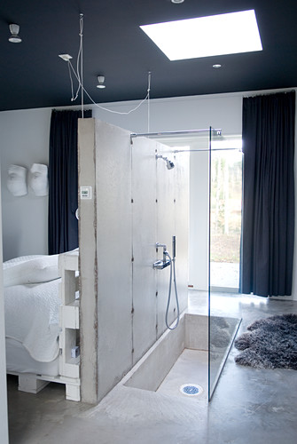 Exposed concrete wall as partition between DIY bed and combination bathtub and shower sunk in concrete floor with glass screen