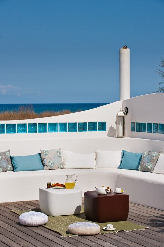 Sunny roof terrace with masonry bench and floor cushions next to side tables