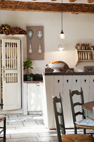 Wooden chairs, counter and cupboard with turned spindle doors in rustic kitchen