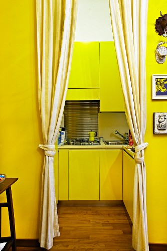 Yellow-painted foyer with gathered curtains at open doorway with view into modern fitted kitchen