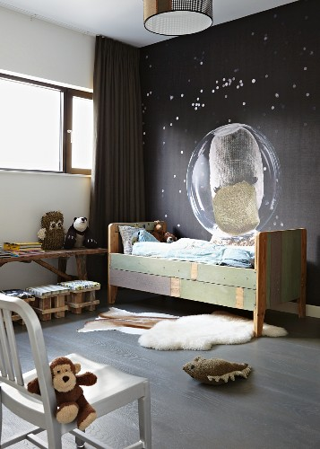 Eclectic child's bedroom- vintage bed against dark wall with space motif and soft toys on chair and floor