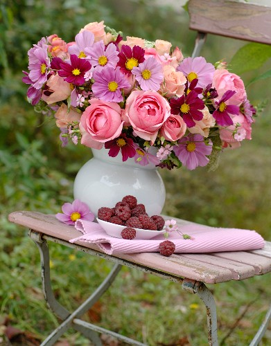 Pink summer bouquet and dish of raspberries on old folding chair in garden