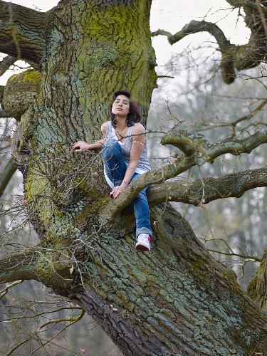 Dark-haired woman sitting in tree