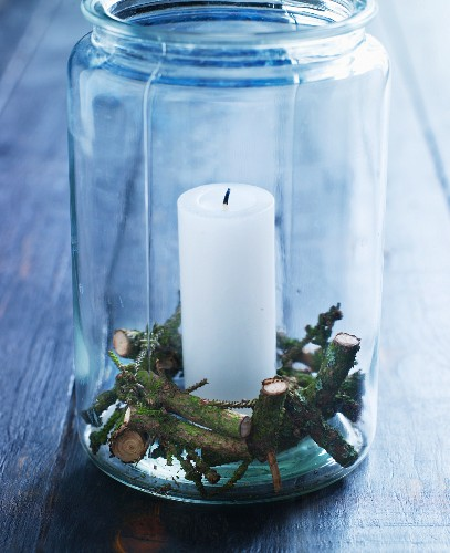 Candle and pieces of spruce twig in preserving jar