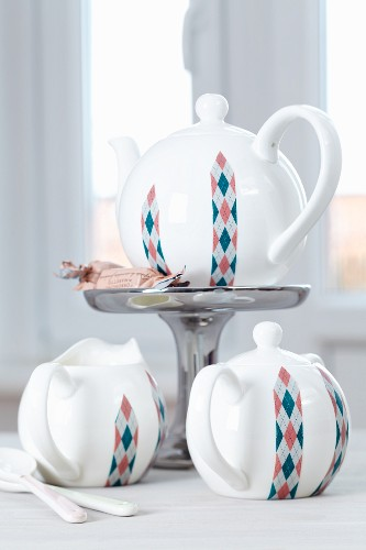 White tea service decorated with strips of Argyle-patterned tape