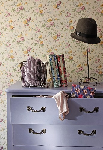 Old hat on vintage hatstand on top of Baroque chest of drawers painted purple with clothing spilling from open drawer against wall with floral wallpaper