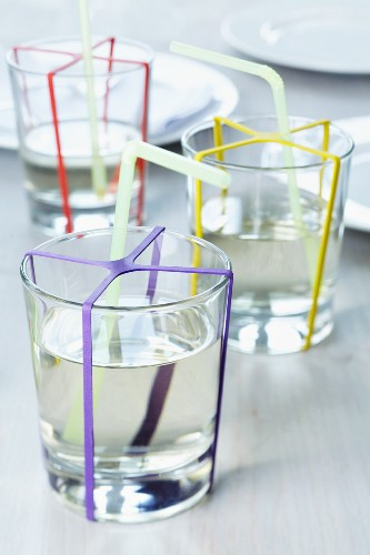 Glasses of water decorated with colourful rubber bands