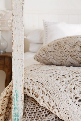 Knitted cushion and crocheted throw in natural-coloured yarns next to wooden post of old bedstead