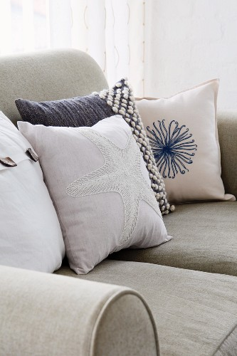 Various scatter cushions in maritime style on sofa with stone grey linen upholstery