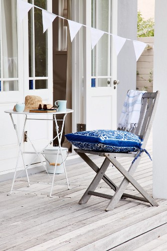 Teak chair with blue and white cushion and bistro table on greyed wooden terrace; open glass door and bunting hung diagonally in background