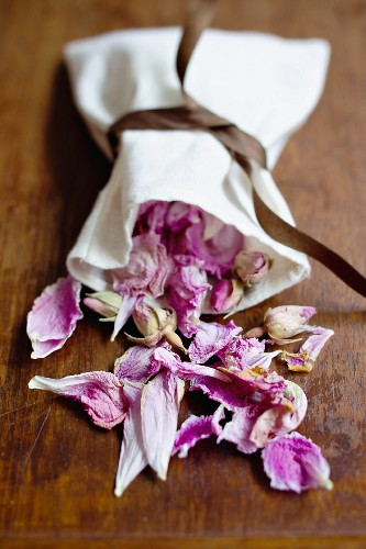 Dried rose petals falling out of a linen sack