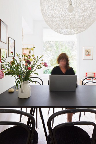 Woman working on dining table - designer pendant lamp above vase of flowers on black table