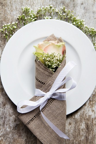 A place setting with a rose and gypsophila