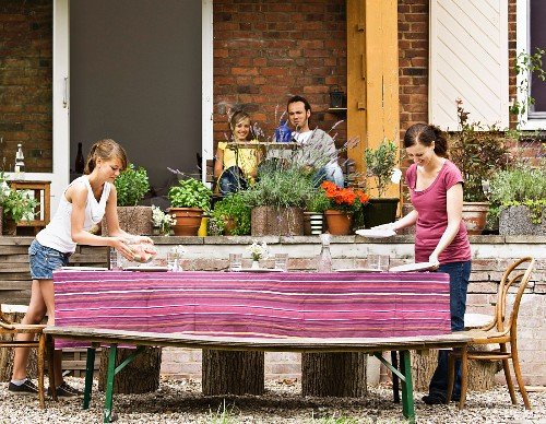 Young girl and woman setting the table