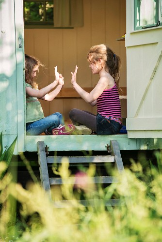 Two girls sitting and playing in the entrance to a small summer house