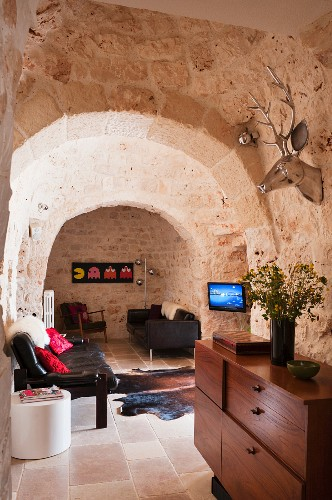 Graham and Green deer head above a sideboard and leather sofa in a the living room of a trullo