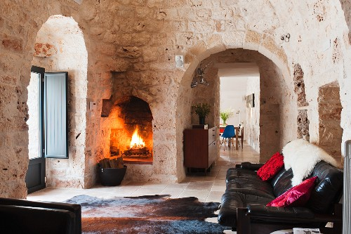 Black leather sofa and animal skin rug in the living room of a trullo
