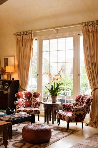 Pair of matching armchairs upholstered in Kathryn Ireland fabric and moroccan leather pouffe in living room with coved ceiling