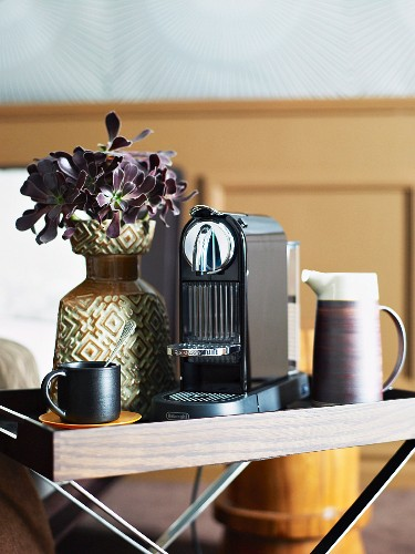 Modern coffee machine and retro vase of flowers on folding tray table