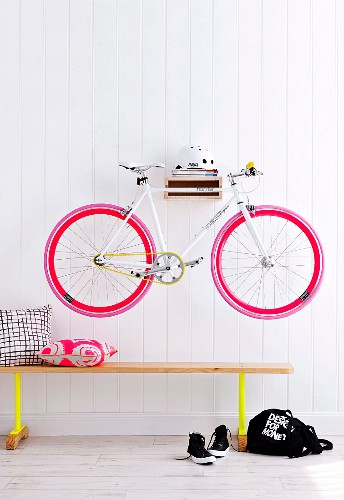 Bicycle hung on hall wall above a bench
