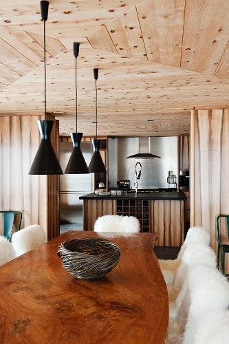 Chalet dining area with polished, live-edge, wooden table top, black designer lamps and view into kitchen area