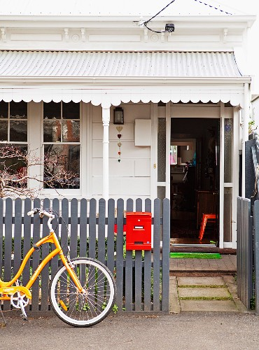 Entrance of white-painted cottage with porch; yellow bicycle leaning on grey garden fence with red letter box