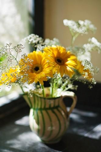 Yellow gerbera daisies in green striped ceramic jug on window sill