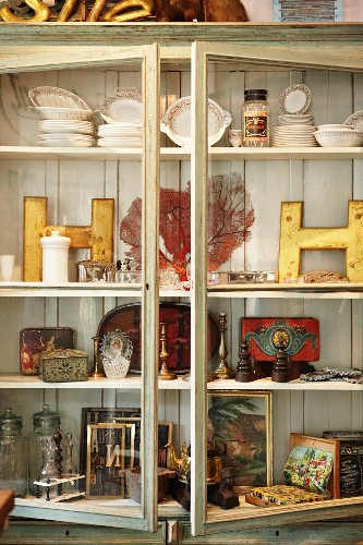 Display case filled with hotchpotch of vintage objet from crockery to picture frames