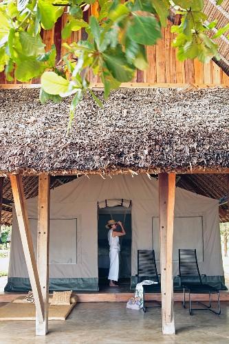 Frau in der Öffnung eines grossen Schlafzeltes mit Holzpodest und Dachkonstruktion aus Holz mit Strohdeckung; Liegemöbel vor dem Zelt