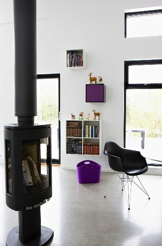 Free-standing log burner and classic, black shell chair in modern living room