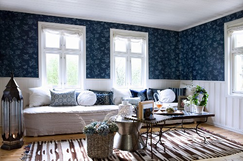 Comfortable living room with various side tables in front of long bench below window and white, half-height wood panelling below blue patterned wallpaper