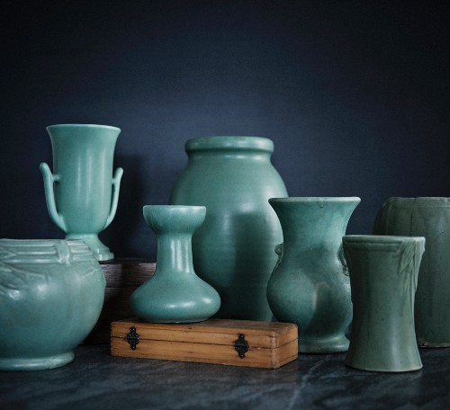 Range of different hand-thrown vases with light green glaze against black background