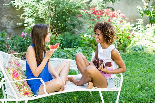 Two women sitting on a sun lounger with a slice of melon and a guitar