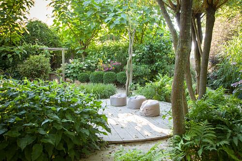 Pouffes on round wooden deck in green summery garden