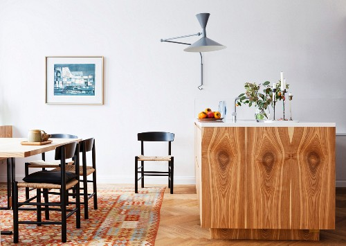 Island counter with wood-grained front and dining area on patterned carpet