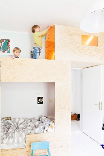 Children playing on custom bunk beds with play house