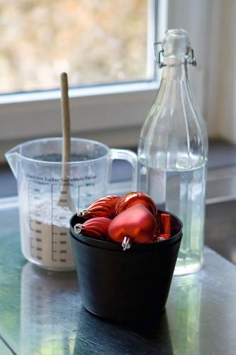 Rote Weihnachtsbaumanhänger vor Gips und einer Wasserflasche