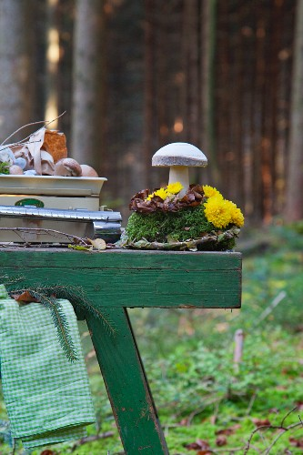 Button mushrooms on scales and wooden toadstools on arrangement of moss and flowers