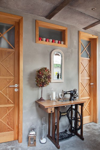 Sewing machine decoratively arranged between two country-house interior doors against concrete wall