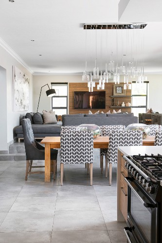 Upholstered chairs around dining table in open-plan interior