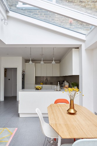 Bright dining area below skylight and view of white fitted kitchen