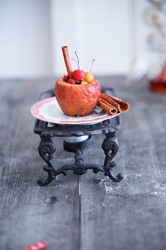 Baked apple and cinnamon stick on vintage warmer