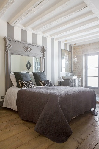 Double bed with headboard made from old fire surround and integrated mirror against striped wall with sink in background