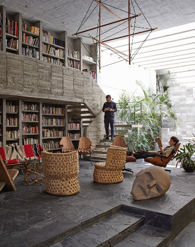 Man and woman in open-plan interior of concrete house