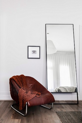 Brown armchair with leather cover next to standing mirror