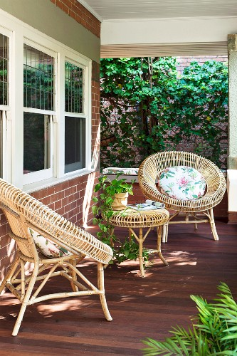 Veranda with brown deck and round wicker furniture