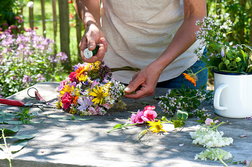 Tying colorful summer flowers wreath