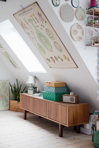 Retro sideboard below botanical illustration on sloping ceiling