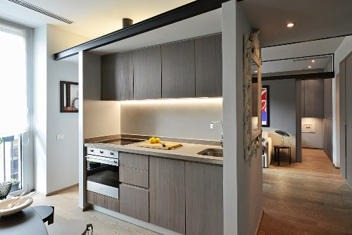 Minimalist fitted kitchen with indirect lighting in apartment