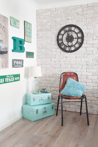 Mint-green suitcases in corner below retro signs and clock on walls